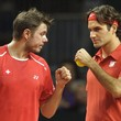 Swiss Davis Cup tennis player Stanislas Wawrinka, left, and teammate Roger Federer, right, react after a winning point against US Davis Cup tennis players Mardy Fish and Mike Bryan during the Davis Cup World Group first round double match between Switzerland and the US in the Forum Arena in Fribourg, Switzerland, Saturday, Feb. 11, 2012. (AP Photo/Keystone, Laurent Gillieron)